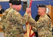 New Garrison Commander Col. Hui Chae Kim (right) passes the garrison flag back to Command Sgt. Maj. Frank Mathias, garrison command sergeant major, after taking command May 19, 2018, at Rumpel Fitness Center at Fort McCoy, Wis. Kim took command of the garrison from Col. David J. Pinter Sr. The change-of-command ceremony took place at the same time as the 2018 Armed Forces Day Open House at the installation. (U.S. Army Photo by Scott T. Sturkol, Public Affairs Office, Fort McCoy, Wis.)