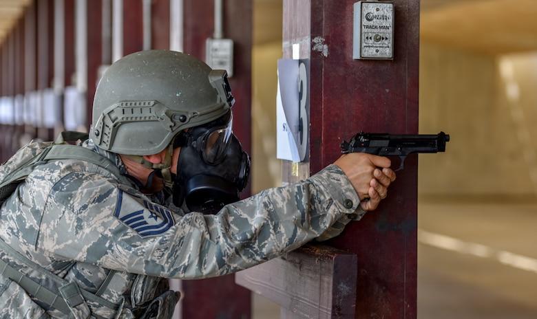 Airmen uses wooden beam to brace himself while firing M9 pistol.