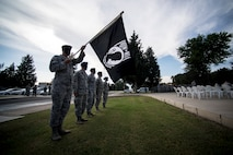 Airmen hold POW/MIA flag during retreat ceremony