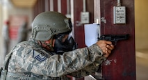 Airmen braces himself against wooden beam while firing in M9 pistol firing competition.