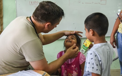 An Air Force doctor examines a child in Panama.