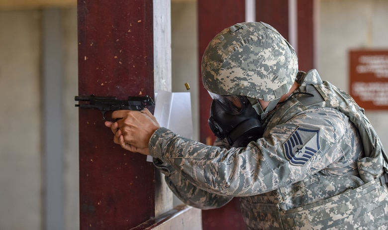 Airmen fires M9 during pistol firing competition while wearing gas mask.