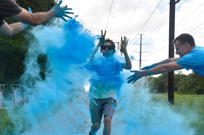A child from the Joint Base Charleston Youth Center runs through colored chalk during a color run May 18, 2018, at JB Charleston, S.C.