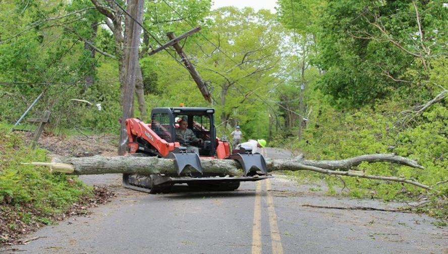 Master Sgt. Jim Mele, Powerproduction Superintendent for the 103rd Civil Engineering Squadron, maneuvers a skid steer to clear the road May 18, 2018 in Bethany, Conn. Experience equipment operators from the 103rd Civil Engineering Squadron responded to the town of Bethany  to assist local and state agencies in route clearance after the storm May 15, 2018. (U.S. Air National Guard photo by 1st Lt. Jen Pierce/released)
