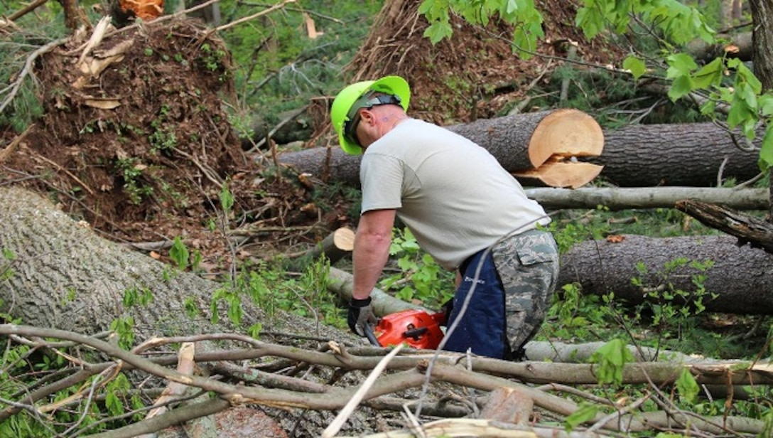 Staff Sgt. Justin Wielock, 103rd Civil Engineering Squadron, uses a chainsaw to cut trees down for removal May 18, 2018 in Bethany, Conn. After the statewide storm on May 15, 2018, the Connecticut National Guard was activated to assist local and state agencies clear roads of fallen trees and debris. (U.S. Air National Guard photo by 1st Lt. Jen Pierce/released)