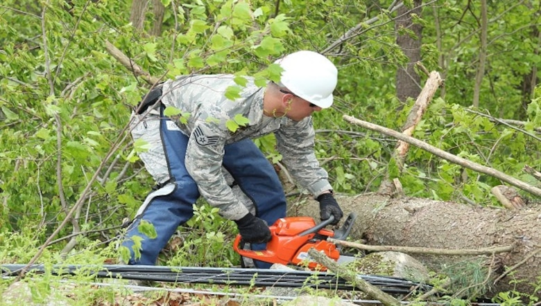 Staff Sgt. Evan Mitchell, 103rd Civil Engineering Squadron, cuts through a downed tree May 18, 2018 in Bethany, Conn. The Connecticut National Guard was activated to assist local and state agencies from the devastation cause by the storm May 15, 2018. (U.S. Air National Guard photo by 1st Lt. Jen Pierce/released)
