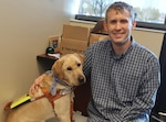 Mason Chronister, an administrative assistant in Distribution's Organization Management/J9 directorate and his guide dog, Xavier.