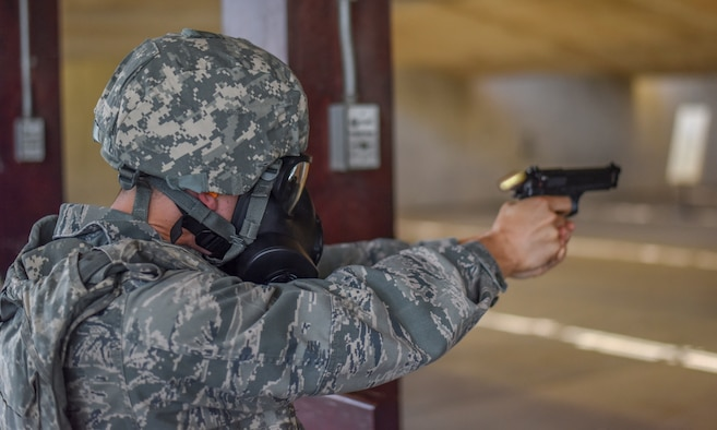 Bullet shell flies backwards as Airman fires M9 pistol.