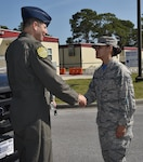 U.S. Air Force Col. Michael Hernandez, 325th Fighter Wing commander, coins Senior Airman Dannyel Butt.
