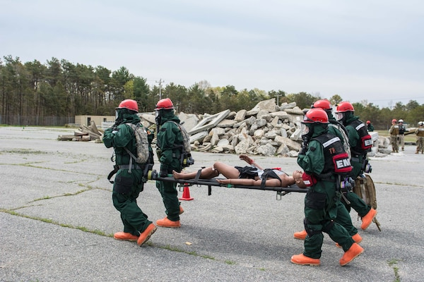 A National Guard search and extraction team carries a dummy away from a collapsed structure as part of an exercise to test the New England Chemical Biological Radiological Nuclear (CBRN) Enhanced Response Package's (CERF-P) response to a CBRN event at Joint Base Cape Cod, Buzzards Bay, Massachusetts May 16, 2018.