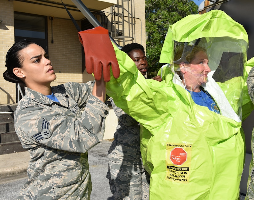 U.S. Air Force Senior Airman Dannyel Butte, 325th Aerospace Medicine Squadron bioenvironmental engineering journeyman, assists Lt. Col. Linda Coates, 325th Aerospace Medicine Squadron commander, don a chemical protective suit.