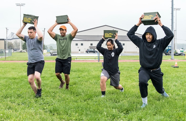 From left, Staff Sgt. Kevin Garcia, Senior Airman Norman Mosby-Hauer, Staff Sgt. Charnelle Albino and Airman 1st Class Daniel Evans, all from the 436th Security Forces Squadron, perform ammo can lunges during the Police Week Combat Fitness Challenge May 17, 2018, at Dover Air Force Base, Del. Upon completing all nine challenges, the team finished in second place posting a time of 6 minutes. (U.S. Air Force photo by Roland Balik)