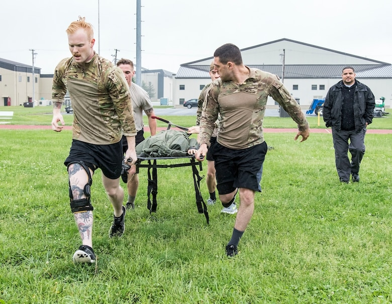 "Detective Alex Gonzalez (back right) watches Senior Airman Donald Maas and Airman 1st Class John Paul Zografos, front left to right, followed by Airman 1st Class Hunter Mowery and Jake Goff, rear left to right, all from the 436th Security Forces Squadron, perform the ""Rescue Randy Pull"" during the Police Week Combat Fitness Challenge May 17, 2018, at Dover Air Force Base, Del. The team finished in first place with a time of 5 minutes and 13 seconds. (U.S. Air Force photo by Roland Balik)"