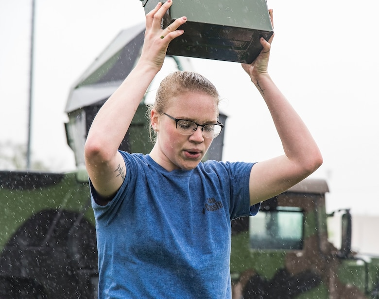 Airman 1st Class Lakyn Wedlock, 436th Security Forces Squadron, performs ammo can lunges in the rain during the Police Week Combat Fitness Challenge May 17, 2018, at Dover Air Force Base, Del. Wedlock and her three teammates completed eight other challenges consisting of a Rescue Randy Pull, fireman's carry, high crawl, tire flip, 100-meter sprint, buddy drag, 50 ruck squats and 50 ruck presses. (U.S. Air Force photo by Roland Balik)