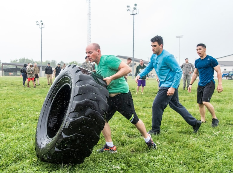 Representing the 436th Communications Squadron, from left, Master Sgt. John Eckert, Senior Airman Jeffrey Bailey-Oqueli, Airman 1st Class Rylan Phungtake turns flipping a tire during the Police Week Combat Fitness Challenge May 17, 2018, at Dover Air Force Base, Del. Five teams completed the nine fitness challenges competing for the fastest overall team time. (U.S. Air Force photo by Roland Balik)