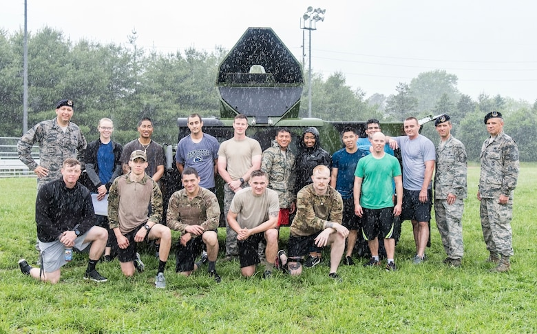 Lt. Col. Michael Morales (left) 436th Security Forces Squadron commander, and Police Week Combat Fitness Challenge participants pose for a photo in the rain after completing the team competition May 17, 2018, at Dover Air Force Base, Del. Morales awarded trophies to the first, second and third place teams. The first place team logged a 9-challenge cumulative time of 5 minutes and 13 seconds. (U.S. Air Force photo by Roland Balik)