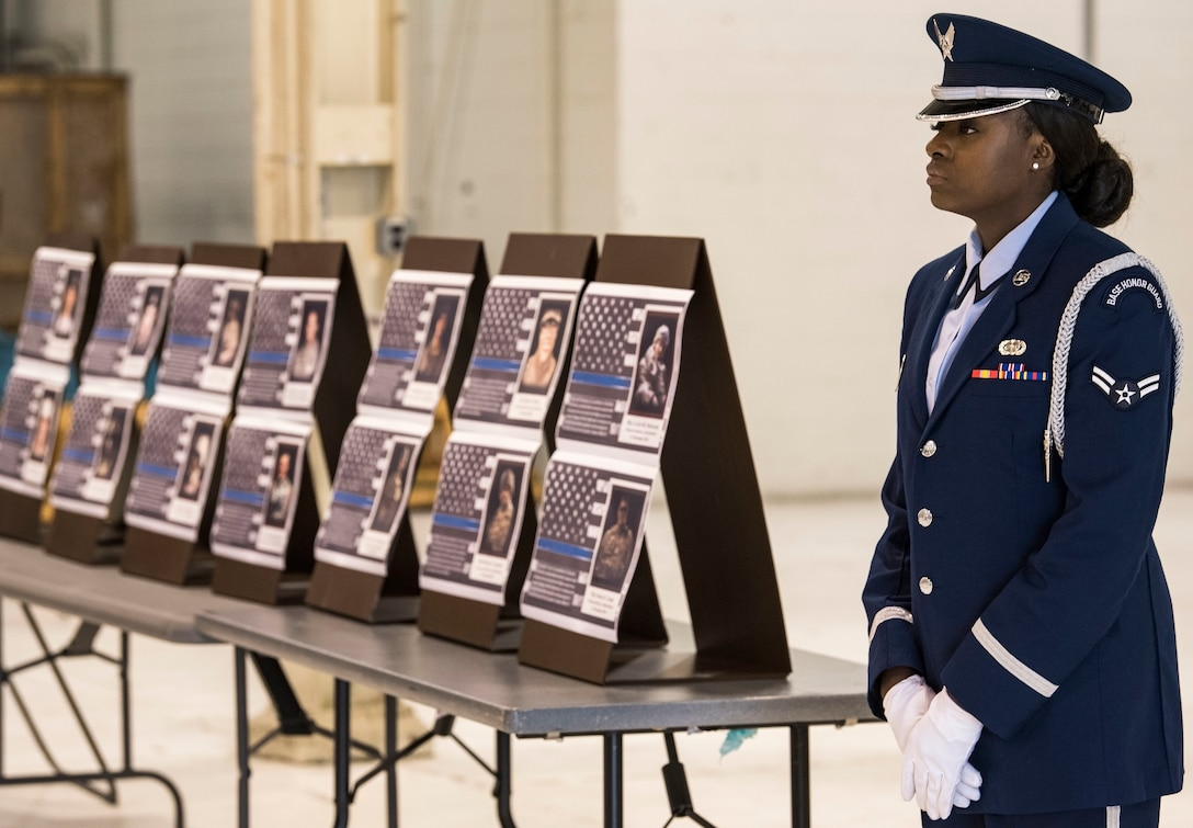 Airman 1st Class Bervely Maxis, 436th Airlift Wing Base Honor Guard member, stands at parade rest prior to the start of the National Police Week Remembrance Ceremony May 18, 2018, at Dover Air Force Base, Del. In the background are 14 placards in honor of Air Force security forces members who have died in the line of duty since 2005. (U.S. Air Force photo by Roland Balik)