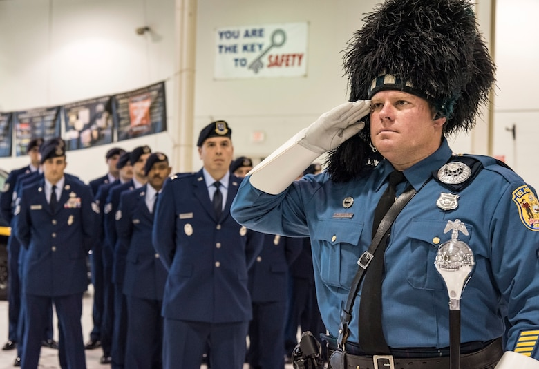 Sgt. Dan Salfas, Delaware State Police Pipes and Drums band drum major, salutes 14 placards during the National Police Week Remembrance Ceremony, May 18, 2018, at Dover Air Force Base, Del. The placards were displayed in honor of Air Force security forces members who died in the line of duty since 2005. The ceremony also recognized 12 Air Force Office of Special Investigation agents who made the ultimate sacrifice in defense of the country. (U.S. Air Force photo by Roland Balik)