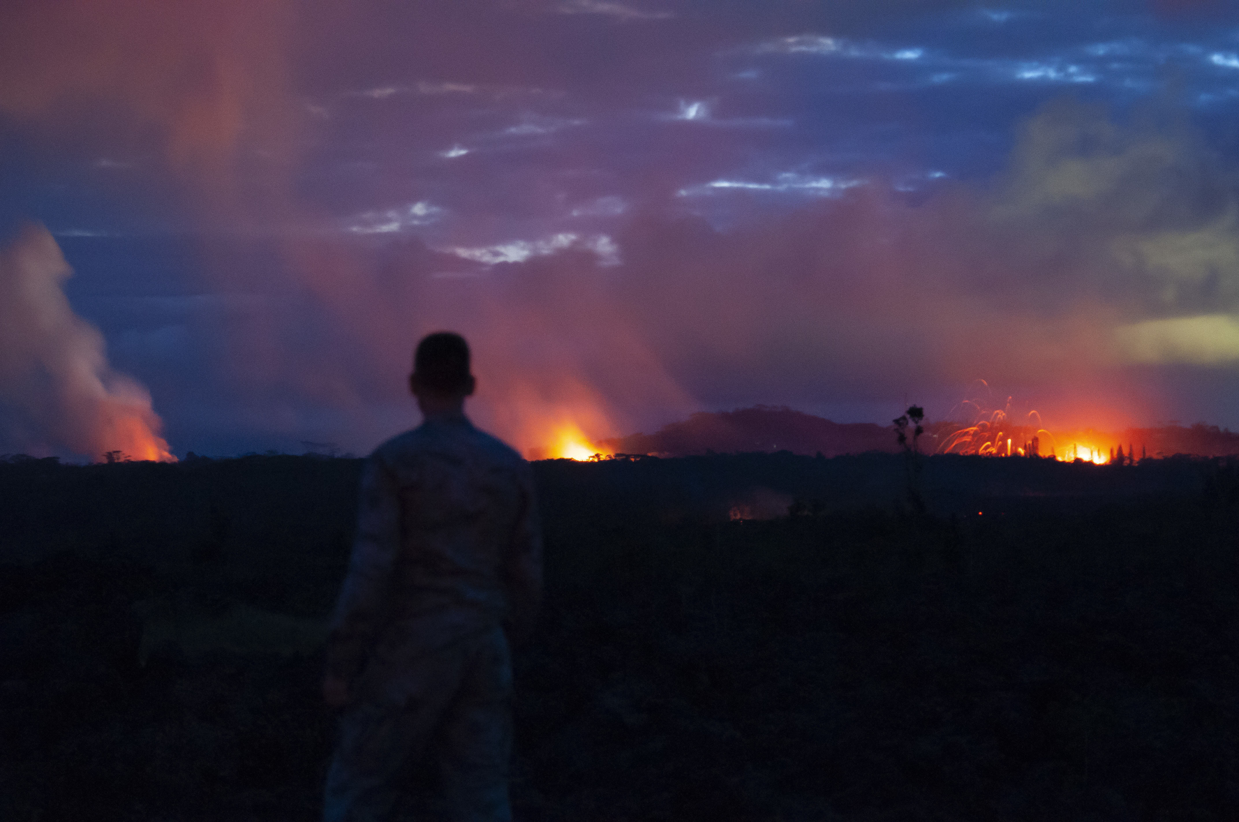 A member of the Hawaii Air National Guard observes three lava fissures