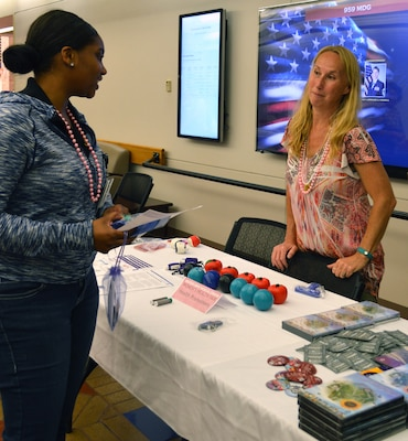 Symone Lofton (left), information desk clerk, talks with Beverly Benson at the health promotions table May 19 at Brooke Army Medical Center's Women's Health Fair.