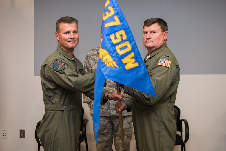 """Col. Devin R. Wooden, 137th Special Operations Wing commander (left), and Col. Kelly W. Cobble, outgoing 137th Special Operations Group commander (right), pose with the 137th SOG guide-on during the Group's change of command ceremony at Will Rogers Air National Guard Base in Oklahoma City, May 17, 2018. Col. Daniel R. """"Pinto"""" Fowler, formerly the Air National Guard's Advisor to U.S. Air Force Special Operations Command, Hurlbert Field, Fla., assumed command with more than 20 years of military experience, including three years as a Joint Terminal Attack Control qualified Air Liaison Officer and 12 years of flying. (U.S. Air National Guard photo by Staff Sgt. Kasey Phipps)"""