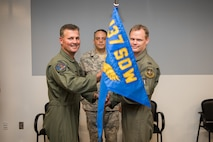 "Col. Devin R. Wooden, 137th Special Operations Wing commander (left), and Col. Daniel R. ""Pinto"" Fowler, incoming 137th Special Operations Group commander (right), pose with the 137th SOG guide-on during the Group's change of command ceremony at Will Rogers Air National Guard Base in Oklahoma City, May 17, 2018. Fowler, formerly the Air National Guard's Advisor to U.S. Air Force Special Operations Command, Hurlbert Field, Fla., assumed command with more than 20 years of military experience, including three years as a Joint Terminal Attack Control qualified Air Liaison Officer and 12 years of flying. (U.S. Air National Guard photo by Staff Sgt. Kasey Phipps)"