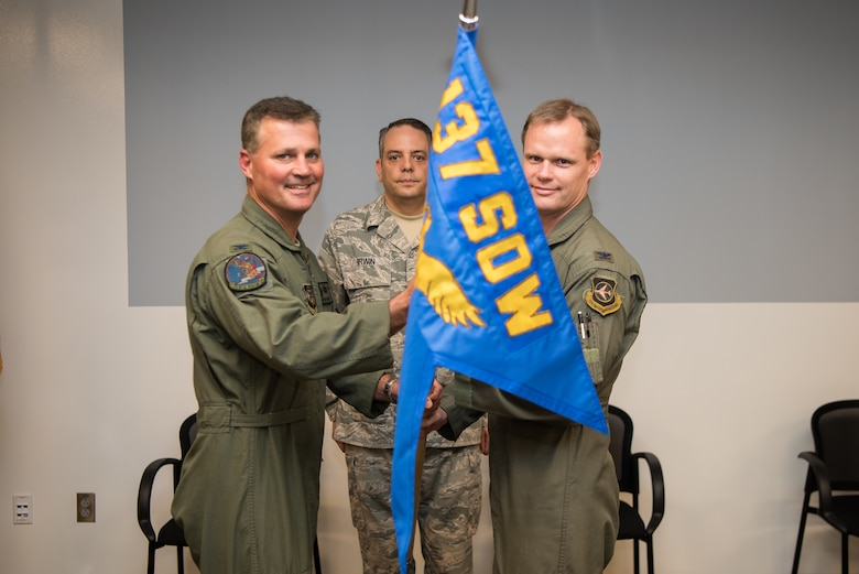 """Col. Devin R. Wooden, 137th Special Operations Wing commander (left), and Col. Daniel R. """"Pinto"""" Fowler, incoming 137th Special Operations Group commander (right), pose with the 137th SOG guide-on during the Group's change of command ceremony at Will Rogers Air National Guard Base in Oklahoma City, May 17, 2018. Fowler, formerly the Air National Guard's Advisor to U.S. Air Force Special Operations Command, Hurlbert Field, Fla., assumed command with more than 20 years of military experience, including three years as a Joint Terminal Attack Control qualified Air Liaison Officer and 12 years of flying. (U.S. Air National Guard photo by Staff Sgt. Kasey Phipps)"""