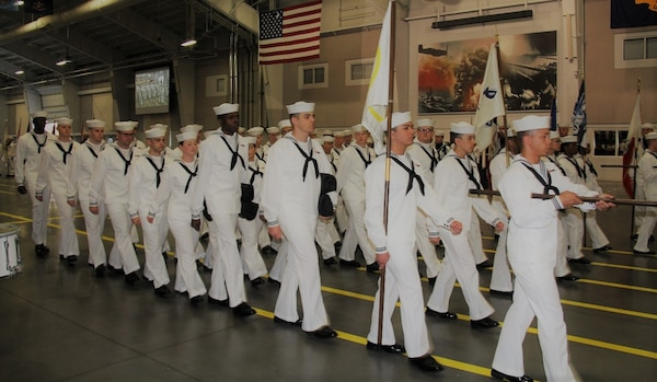 IMAGE: GREAT LAKES, Ill. (May 18, 2018) - Recruit Division 213 marches with the Naval Surface Warfare Center Dahlgren Division Dam Neck Activity flag (blue, at right) at their graduation ceremony. NSWCDD Dam Neck Activity Commanding Officer Cmdr. Andrew J. Hoffman led a contingent at graduation after another contingent participated in the division's Battle Stations 21 drills and Capping Ceremony earlier in the week.