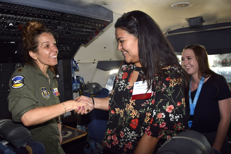 U.S. Air Force Maj. Amy Tullis, 356th Airlift Squadron instructor pilot, shakes hands with Kellea Elliott, an Air Force Personnel Center Premier College Intern Program symposium attendee, while in the C5-M Super Galaxy cockpit during a tour to the 433rd Airlift Wing May 16, 2018, at Joint Base San Antonio-Lackland, Texas. Tullis used her 15 years of piloting experience to brief about the aircraft and answer questions from interns. (U.S. Air Force photo by Tech. Sgt. Iram Carmona)