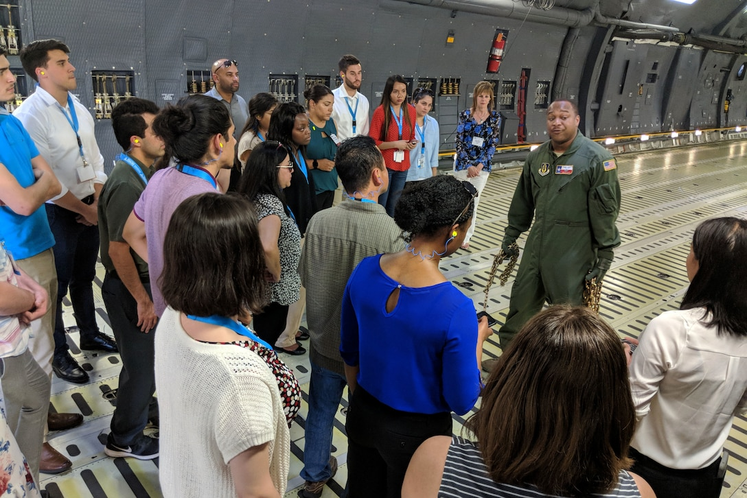 U.S. Air Force Master Sgt. Bryan Boyd, 356th Airlift Squadron loadmaster, gives a brief lesson to college students in what it takes to load a C-5M Super Galaxy during an Air Force Personnel Center Premier College Intern Program symposium tour to the 433rd Airlift Wing May 16, 2018, at Joint Base San Antonio-Lackland, Texas. Tour members were able to handle chains and calculate requirements during the tour. (U.S. Air Force photo by Staff Sgt. Lauren M. Snyder)