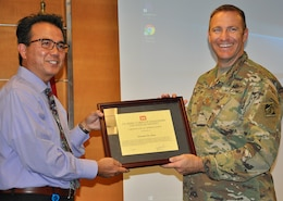 Maj. Scotty Autin, deputy commander for the U.S. Army Corps of Engineers Los Angeles District, right, presents Ed De Mesa, chief of the Planning Division for the LA District, left, with a certificate thanking him for being the speaker at the District's Asian American/Pacific Islander Heritage Month Observance May 22 at the District headquarters in downtown LA.