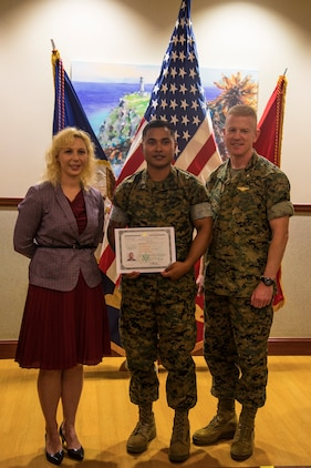 CAMP FOSTER, OKINAWA, Japan – Karen Karas, left, Sgt. Nelson Sigrah, middle, and Brig. Gen. Paul Rock Jr. pose for a picture with Sigrah's naturalization certificate after a naturalization ceremony May 17 hosted at the Ocean Breeze aboard Camp Foster, Okinawa, Japan.