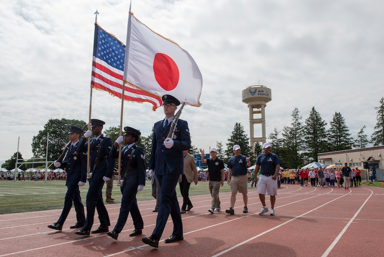 Four Airmen carry the colors at the front of the athlete parade during the Kanto Plains Special Olympics at Yokota Air Base, Japan, May 19, 2018.