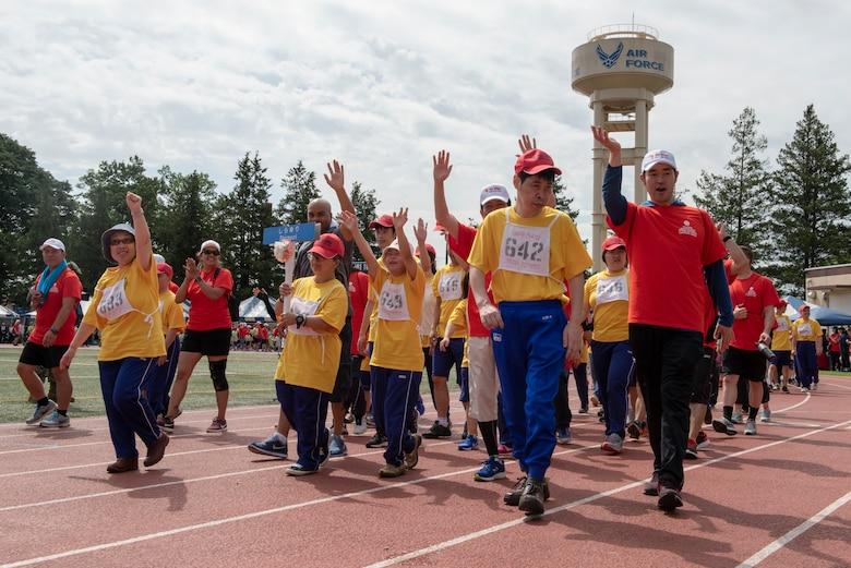 The athletes representing Shirayuri wave to the crowd during the opening parade of the Kanto Plains Special Olympics at Yokota Air Base, Japan, May 19, 2018.