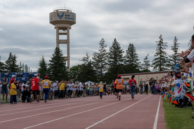 Athletes with their athlete buddies sprint to the finish line of the 50 meter race during the Kanto Plains Special Olympics at Yokota Air Base, Japan, May 19, 2018.