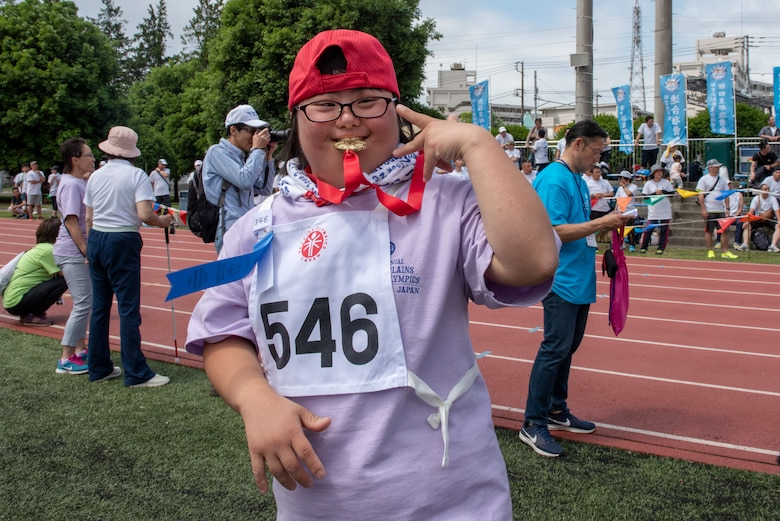 An athlete poses for a photo after winning gold in the 50 meter sprint during the Kanto Plains Special Olympics at Yokota Air Base, Japan, May 19, 2018.