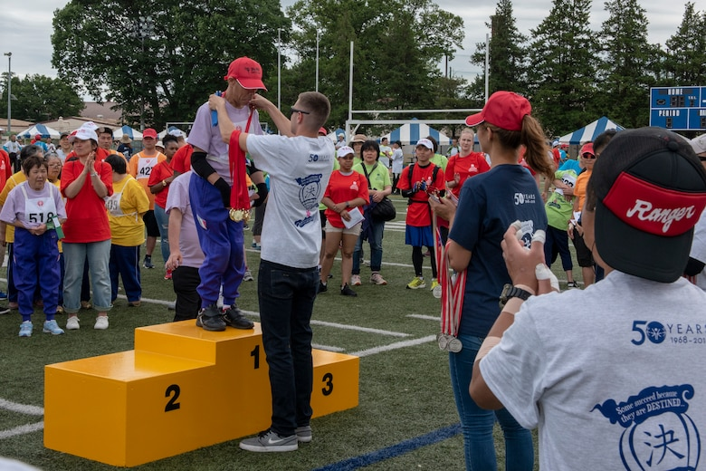 An athlete receives a gold medal as participants cheer him on for his success during the Kanto Plains Special Olympics at Yokota Air Base, Japan, May 19, 2018.