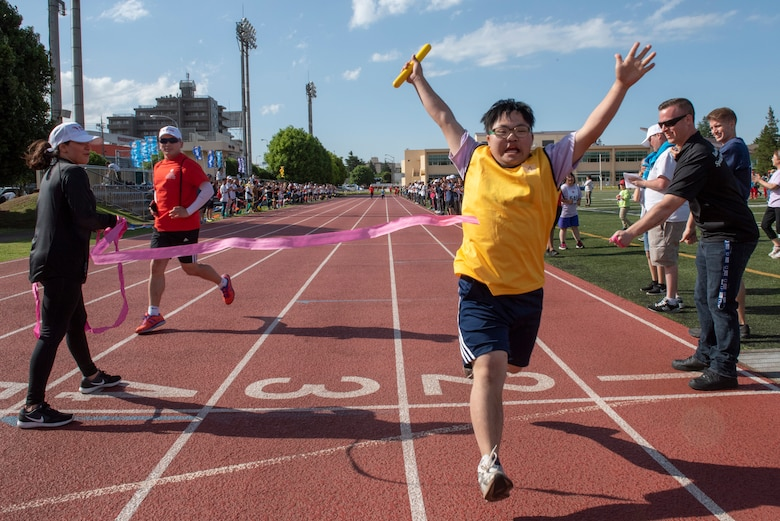 An athlete sprints through the finish line of the 4x100 meter relay race during the Kanto Plains Special Olympics at Yokota Air Base, Japan, May 19, 2018.