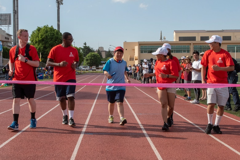 Five volunteer athlete buddies cheer on an athlete during the 4x100 meter relay race during the Kanto Plains Special Olympics at Yokota Air Base, Japan, May 19, 2018.