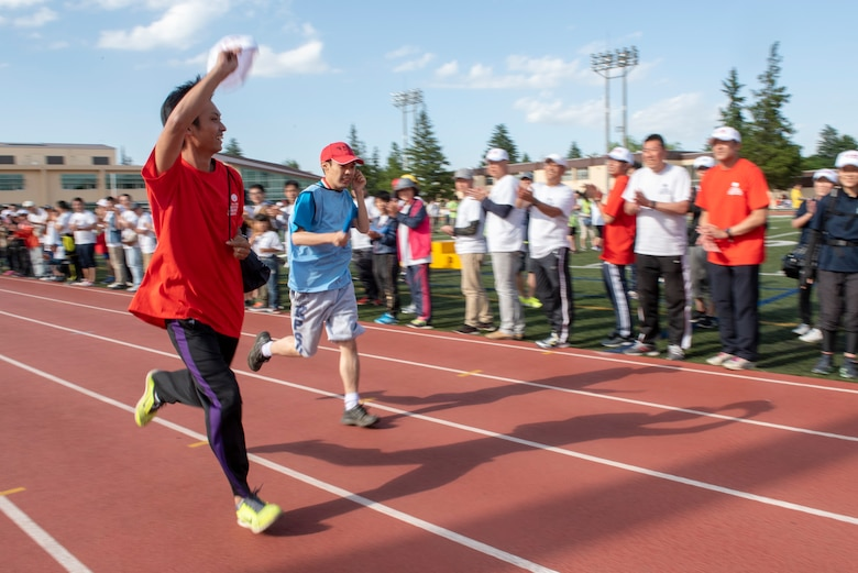 An athlete buddy sprints next to his athlete as the crowd cheers them on during the 4x100 meter relay race during the Kanto Plains Special Olympics at Yokota Air Base, Japan, May 19, 2018.