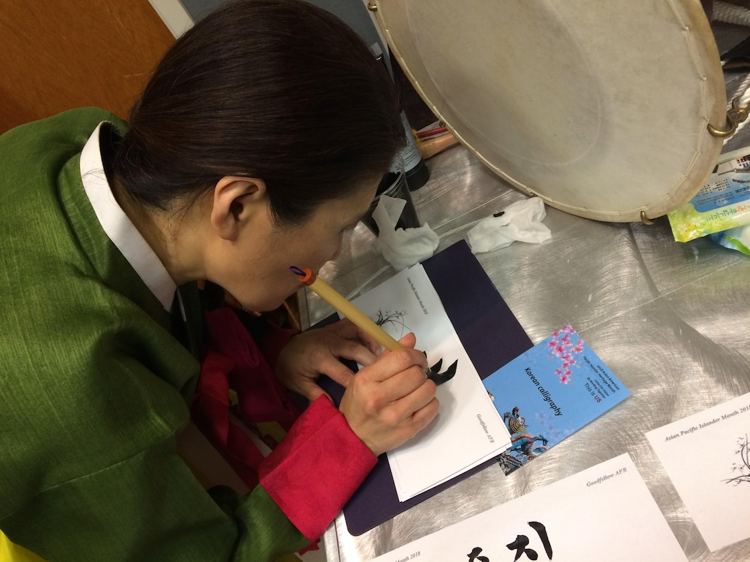A committee volunteer writes the name of an attendee in Korean caligraphy at the Asian American Pacific Islander Heritage event at the Event Center on Goodfellow Air Force Base, Texas, May 18, 2018. The event helped inform base members about the different cultures during AAPIH month. (U.S. Air Force photo by Aryn Lockhart/Released)