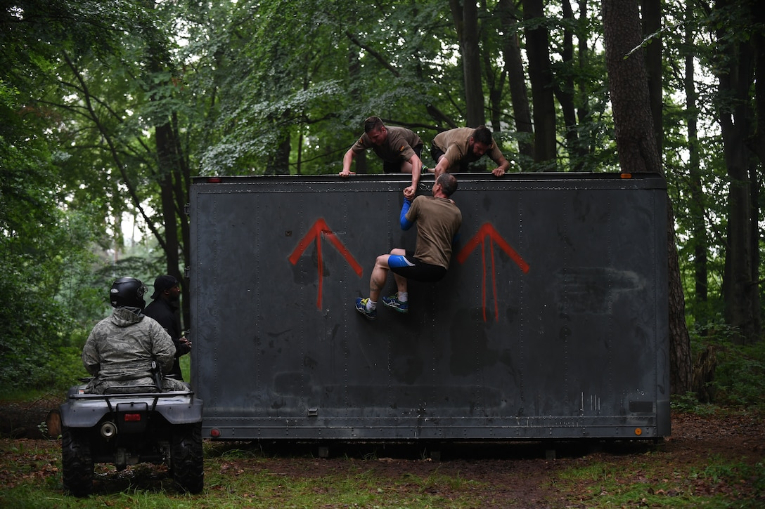 Kaiserslautern Military Community service members work together to climb over a wall during the 2018 Ramstein Mudder, May 24 at Ramstein Air Base, Germany. More than 200 Kaiserslautern Military Community Members ran the 2.5 mile obstacle course for the 86th Airlift Wing's resilience day. (U.S. Air Force photo by Staff Sgt. Nesha Humes Stanton)