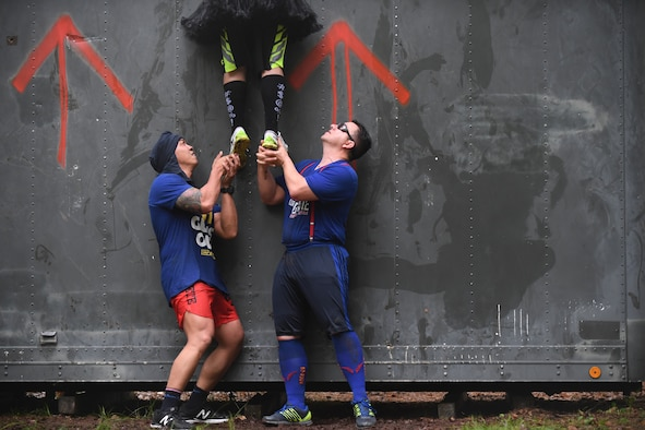 Airmen from the 1st Combat Communications Squadron lift one another over a wall during the 2018 Ramstein Mudder, May 24 at Ramstein Air Base, Germany. More than 200 Kaiserslautern Military Community Members ran the 2.5 mile obstacle course for the 86th Airlift Wing's resilience day. (U.S. Air Force photo by Staff Sgt. Nesha Humes Stanton)