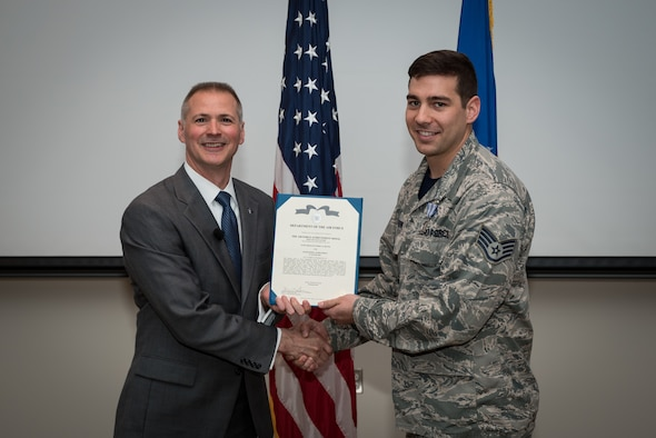 Staff Sgt. Joshua Bevins stands with Dr. Kevin Geiss, Airman Systems Directorate director, after being awarded with the Air Force Achievement Medal. Bevins and another Airman worked as a team to help a choking coworker. (U.S. Air Force photo/Richard Eldridge)
