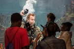 Navy diver plays with children through aquarium glass.