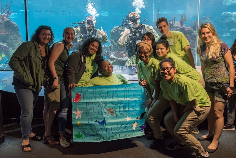 Navy divers pose in water inside New York Aquarium.
