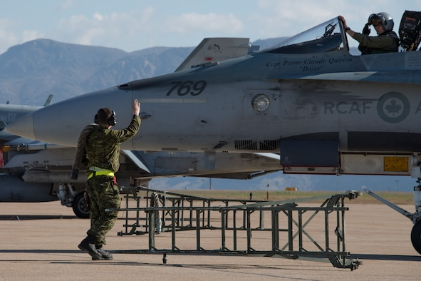 Royal Canadian Air Force structural technician Cpl. Matthew Roy salutes pilot Capt. Jason Berndt, both assigned to the 433rd Tactical Fighter Squadron, before takeoff May 3, 2018, at Hill Air Force Base, Utah. The Canadian unit participated in a Weapons Evaluation Systems Program, or WSEP, exercise conducted by the 86th Fighter Weapons Squadron, a Hill tenant unit. (U.S. Air Force photo by R. Nial Bradshaw)