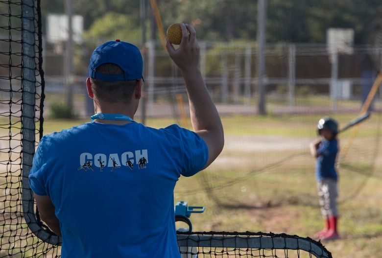 U.S. Air Force Capt. Joshua Gradaille, 33rd Fighter Wing executive officer, shows a practice ball to one of his players before putting it in a pitching machine May 10, 2018, at Eglin Air Force Base, Fla. Gradaille started coaching children's baseball on base more than two years ago when he found himself watching his son from the bleachers and feeling he could make an impact. (U.S. Air Force photo by Staff Sgt. Peter Thompson)