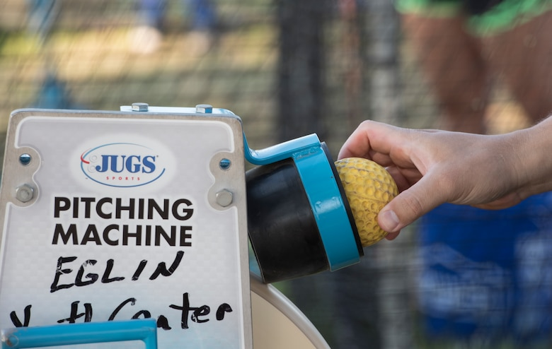 U.S. Air Force Capt. Joshua Gradaille, 33rd Fighter Wing executive officer, places a practice ball in a pitching machine May 10, 2018, at Eglin Air Force Base, Fla. Gradaille's lifelong connection to baseball began as a young boy in Miami Beach, Fla., and eventually led him to coaching his son's team. (U.S. Air Force photo by Staff Sgt. Peter Thompson)