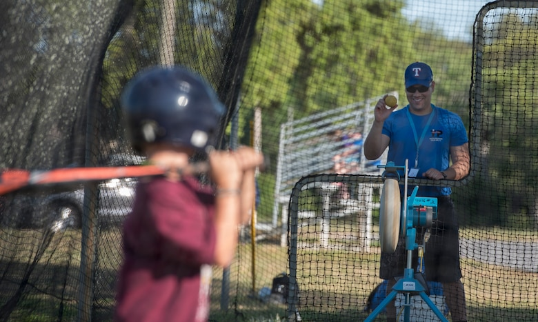 U.S. Air Force Capt. Joshua Gradaille, 33rd Fighter Wing executive officer, shows a practice ball to one of his players before putting it in a pitching machine May 10, 2018, at Eglin Air Force Base, Fla. Gradaille enrolled his son in baseball when he was five years old to instill the many life lessons he feels team sports offer a child. (U.S. Air Force photo by Staff Sgt. Peter Thompson)